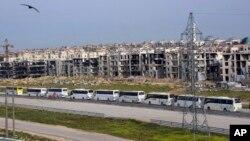 叙利亚官方通讯社萨那发布的图片显示,从两个亲政府村庄撤离的叙利亚平民乘坐大巴车抵达阿勒颇郊区交战双方之间的一个移交地点。(2017年4月21日)