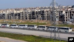 FILE - In this photo released by the Syrian official news agency SANA, buses carry Syrian citizens, who evacuated from the two pro-government villages of Foua and Kfarya, arrive at a handover point between the two sides on the outskirts of Aleppo, Syria, April 21, 2017.