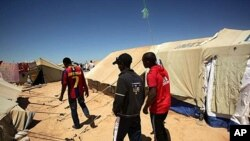 The three Ethiopian friends who survived more than two weeks adrift in the Mediterranean wander through Choucha Camp