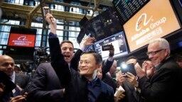 阿裏巴巴的創始人馬雲(中)在公司在紐約證券交易所進行首次公開募股(IPO)時,舉起了敲鍾用的槌子(2014年9月19日)。
