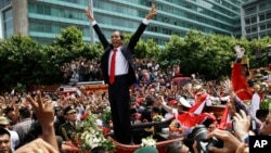 Indonesian President Joko Widodo gestures to the crowd during a street parade following his inauguration in Jakarta, Indonesia, Oct. 20, 2014. (AP Photo/Achmad Ibraham)