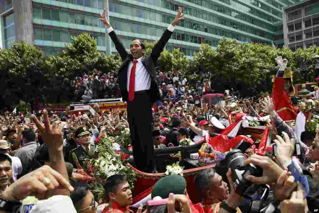 Indonesian President Joko Widodo gestures to the crowd during a street parade following his inauguration in Jakarta, Indonesia, Oct. 20, 2014.
