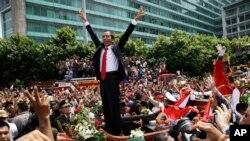 Presiden Joko Widodo memberikan salam kepada seluruh masyarakat yang memadati jalanan Jakarta, dalam pawai menuju Monas, seusai pelantikannya sebagai Presiden (20/10).