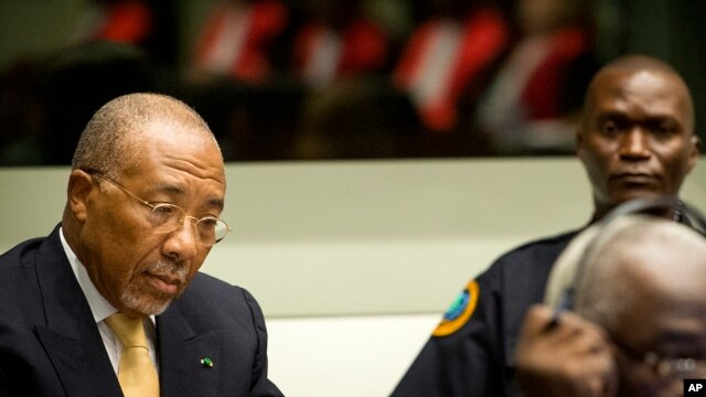 Former Liberian President Charles Taylor, left, pictured at the Special Court for Sierra Leone near The Hague, Netherlands, Sept. 26, 2013.