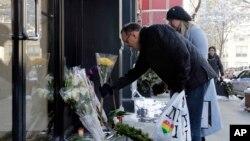 一对男女在演员菲利普•霍夫曼生前居住的纽约公寓楼外放置鲜花,以示悼念。(2014年2月4日)