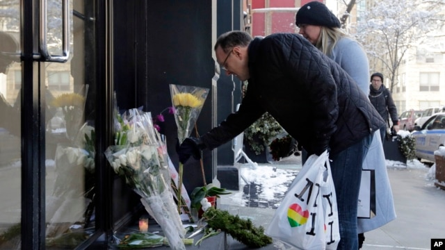 A couple adds to the flowers placed outside the apartment building of actor Phillip Seymour Hoffman, in New York, Feb. 4, 2014.