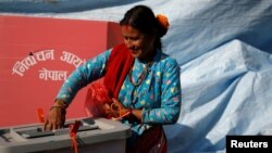 A woman smiles as she cast her vote on a ballot box during the parliamentary and provincial elections in Sindhupalchok District, Nepal, Nov. 26, 2017.