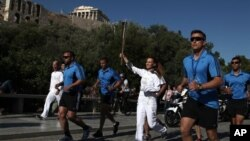 Koreografer penyalaan obor olimpiade di Olympia, Artemis Ignadiou (tengah), membawa obor melewati Parthenon di Athena (16/5). Obor Olimpiade akan dibawa ke London, dan Olimpiade akan segera digelar di kota tersebut 27 Juli hingga 12 Agustus mendatang.