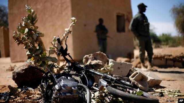 Malian soldiers stand by a motorcycle used by a suicide bomber at the entrance of Gao, northern Mali, Feb. 8, 2013.