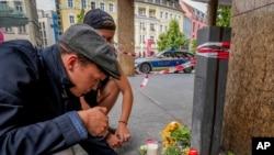 Flores e velas são colocadas na cena do crime no centro de Wuerzburg,Alemanha, Sábado, Junho 26, 2021.