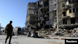 效忠叙利亚总统阿萨德的部队一名成员拿着武器走过政府军控制的阿勒颇城区的一座楼房废墟。(2016年12月9日)