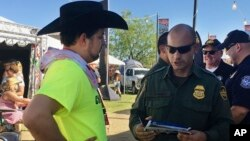 In this April 6, 2017 photo, a U.S. Border Patrol agent gives information about working for the agency to 24-year-old Ric Kindle, of the Phoenix area, at the Country Thunder Music Festival in Florence, Ariz.