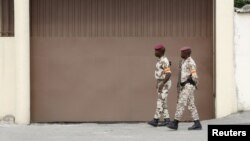 Soldiers walk in front of the headquarters of Constitutional Council before the proclamation of the final list of candidates for the presidential election in Abidjan, Ivory Coast, Sept. 9, 2015.