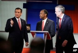 Republican presidential candidates Sen. Ted Cruz, left, retired neurosurgeon Ben Carson and former Florida Gov. Jeb Bush chat during the Fox Business Network Republican presidential debate at the North Charleston Coliseum in North Charleston, S.C., Jan. 14, 2016.
