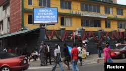 "Pedestrians walk past a sign reading ""Ebola Disease Outbreak"" outside the Ministry of Finance in Monrovia, Liberia, Jan. 12, 2015."