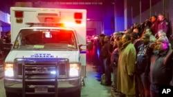 Dolientes saludan el paso de una ambulancia con los cadáveres de los dos policías asesinados cuando eran transportados desde el Centro Médico Woodhull, en Nueva York.