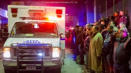 人们在运送两位被杀警员遗体的车辆旁默哀