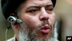 The self-styled cleric, Abu Hamza al-Masri, leads his followers in prayer in the street outside Finsbury Park Mosque, London, Friday Jan. 23, 2004