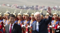 U.S. Vice President Joe Biden, right, waves as he walk with Mongolian Prime Minister Batbold Sukhbaatar after they inspected honor of guards upon arrival at the Chinggis Khaan International Airport in Ulan Bator, Mongolia, Monday, Aug. 22, 2011. (AP Photo