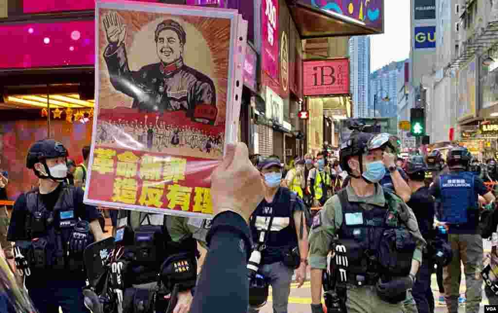 有香港市民10月1日下午在銅鑼灣崇光百貨附近,對著警方封鎖線高舉文化大革命標語。(美國之音湯惠芸)