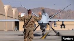 Un aviateur américain guide un drone Reaper MQ-9 de la Force aérienne américaine sur la piste de l'aérodrome de Kandahar en Afghanistan, le 9 mars 2016.