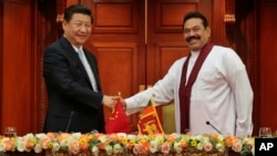 Sri Lankan President Mahinda Rajapaksa, right, shakes hands with Chinese President Xi Jinping during their meeting in Colombo, Sri Lanka, Sept.16, 2014.