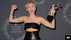 FILE - Miley Cyrus poses with the Video of the Year award in the press room at the MTV Video Music Awards in Inglewood, California, Aug. 24, 2014.