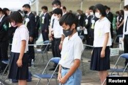 Warga menjaga jarak sosial saat mengheningkan cipta untuk menghormati para korban bom atom 1945 dalam upacara peringatan 76 tahun pengeboman di Nagasaki, di Taman Perdamaian Nagasaki di Nagasaki, Jepang, 9 Agustus 2021. (Kyodo/via REUTERS)