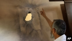 A Palestinian man points at a damaged ceiling of a house following an Israeli airstrike in Nuseirat refugee camp, June 3, 2012.