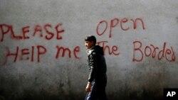 Un migrant passe devant des graffiti à Belgrade, Serbie, le 21 mars 2017.