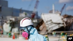 FILE - A Tokyo Electric Power Co. (TEPCO) employee, wearing a protective suit and a mask, walks in front of the No. 1 reactor building at the tsunami-crippled Fukushima Dai-ichi nuclear power plant in Okuma, Fukushima Prefecture, northeastern Japan, Wedne