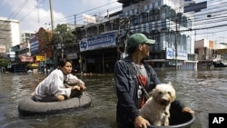 A Thai resident uses a makeshift float to keep his dog dry as he pulls a woman along flooded streets in Rangsit district at the outskirts of Bangkok, Thailand, October 21, 2011.