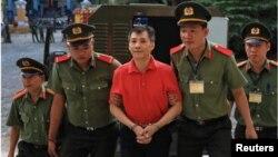 """Công dân Mỹ Michael Nguyen được an ninh hộ tống trước phiên xử tại Tòa án Nhân dân TP Hồ Chí Minh hôm 24/6. Ông Micheal bị kết án 12 năm tù về tội """"lật đổ chính quyền nhân dân"""" theo điều 109 Bộ luật Hình sự Việt Nam. (REUTERS/Stringer)"""