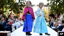 "FILE - Child models are seen dressed up as Anna (L) and Elsa (R) from Disney's ""Frozen"" movie at a Halloween fashion show."