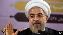 Iranian President Hassan Rouhani gestures as he speaks during a press conference in Tehran, Iran, Saturday, June 14, 2014.