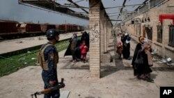 Los civiles iraquíes huyen a través de una estación de tren dañada durante las luchas entre las fuerzas de seguridad iraquíes y los militantes del Estado islámico, en el lado occidental de Mosul, Irak, el domingo 19 de marzo de 2017.
