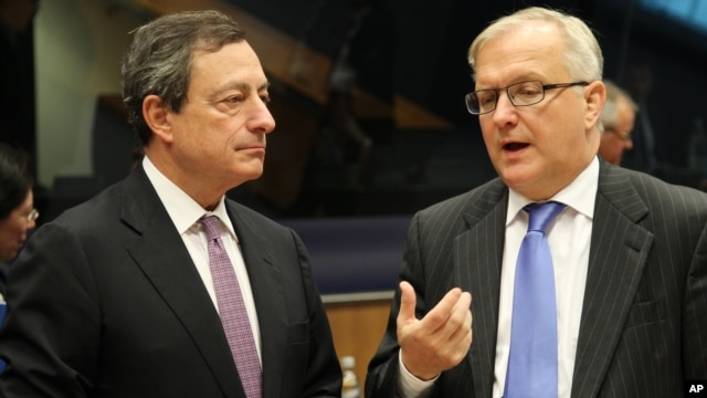President of the European Central Bank Mario Draghi, left, listens to European Commissioner for Economic and Monetary Affairs Olli Rehn, during the Eurogroup meeting, in Luxembourg, October 8, 2012.