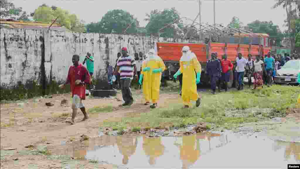 Health workers surround an Ebola patient who escaped from the Elwa Hospital, Paynesville, Liberia, Sept. 1, 2014 .