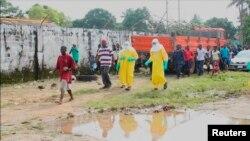 Un libérien atteint d'Ebola escorté par des membres du corps médical à Monrovia