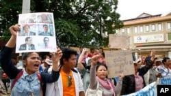 Một người ủng hộ của Đảng Cứu nguy Dân tộc giơ cao chân dung của các nhà lập pháp đảng đối lập bị buộc tội cầm đầu phong trào nổi loạn trước Tòa án Phnom Penh, Campuchia, 17/7/2014.