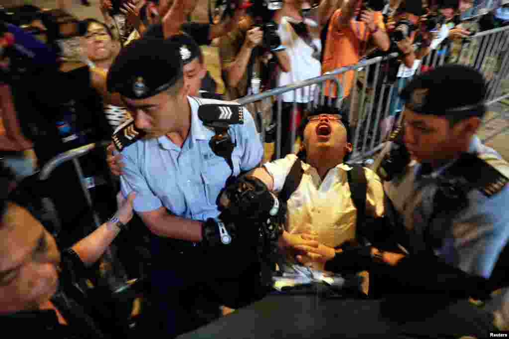 Student protest leader Joshua Wong shouts as he is carried by policemen as protesters are arrested at a monument symbolising the city's handover from British to Chinese rule, a day before Chinese President Xi Jinping is due to arrive for the celebrations, in Hong Kong.
