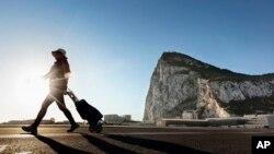 Seorang perempuan berjalan di wilayah Spanyol dekat perbatasan dengan wilayah Inggris di Gibraltar, dengan batu karang Gibraltar tampak di belakang, di kota La Linea de la Concepcion, Spanyol (foto: dok).