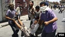 Manifestantes cargan un herido durante choques con la policía en la ciudad de Taiz.