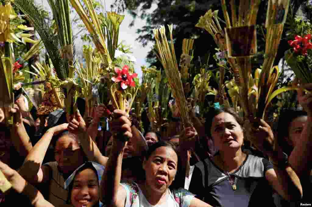 អ្នកកាន់សាសនាកាតូលិកហ្វីលីពីនទទួលពរនៅមុនកម្មវិធីសូត្រធម៌ Palm Sunday នៅក្នុងព្រះវិហារកាតូលិកមួយនៅក្នុងក្រុង Paranaque ប្រទេសហ្វីលីពីន។