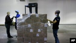 Dr. Abhu Kaur of Khalsa Aid USA, a global humanitarian organization, labels a pallet of electrical transformers, which will be shipped to New Delhi with oxygen concentrators this week, on New York's Long Island, Friday, May 7, 2021. (AP Photo/Jessie Warda