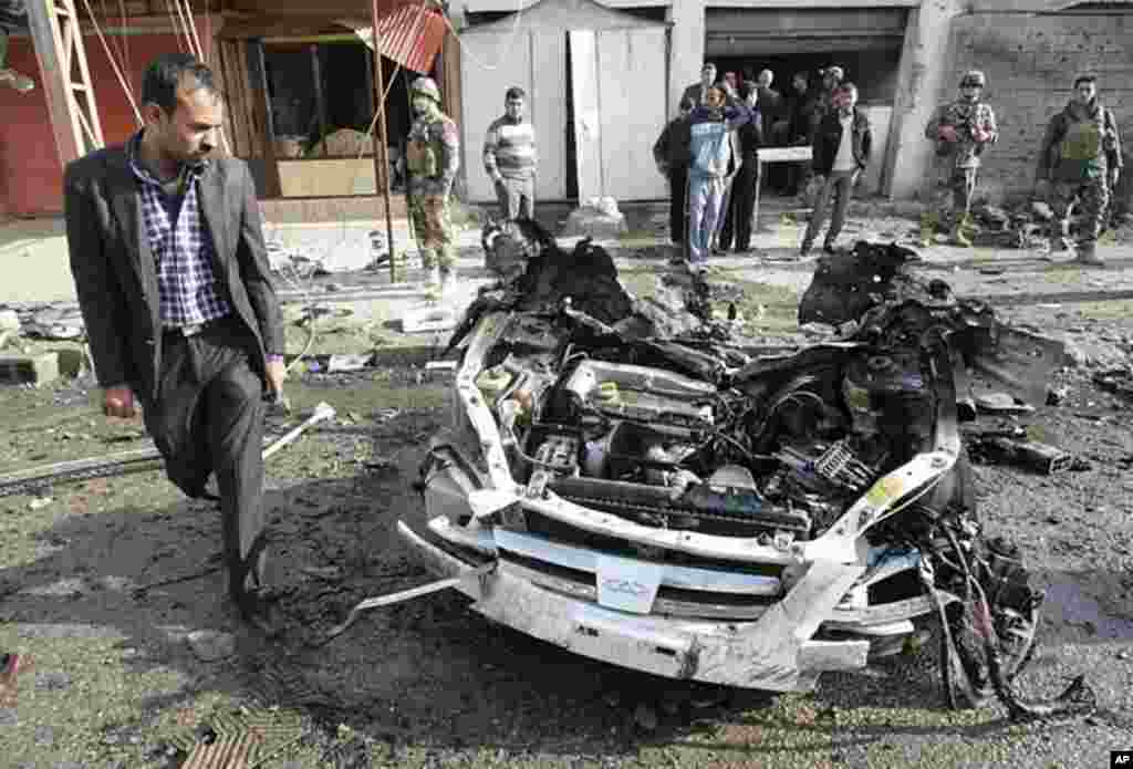 A man walks past the remains of a vehicle used in a bomb attack in Kirkuk, 250 km (155 miles) north of Baghdad. Two car bombs exploded in a quick succession in different districts wounding 20 people, including 15 policemen, in Kirkuk, February 23, 2012.