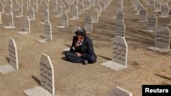 یک کرد عراقی در قبرستان قربانیان حمله شیمیایی سال ۱۹۸۸ یا کشتار انفال