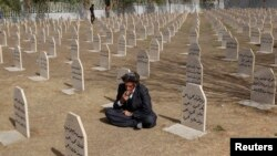 An Iraqi Kurd resident visits the cemetery for victims of the 1988 chemical attack in the Kurdish town of Halabja, which was part of the al-Anfal campaign.