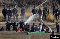 FILE - Police use pepper spray against protesters trying to cross a stream near an oil pipeline construction site near Standing Rock Indian Reservation, north of Cannon Ball, North Dakota, Nov. 2, 2016.