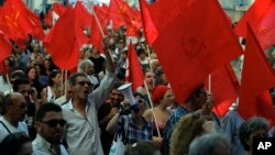 People shout slogans during a protest by the Portuguese Communist party, demanding the breakup of the Portuguese parliament and early elections, in Lisbon, July 3, 2013.